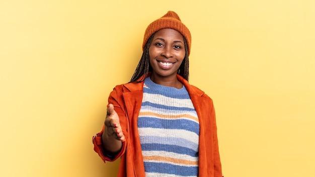 Mujer bonita afro negra sonriendo, luciendo feliz, confiada y amigable, ofreciendo un apretón de manos para cerrar un trato, cooperando