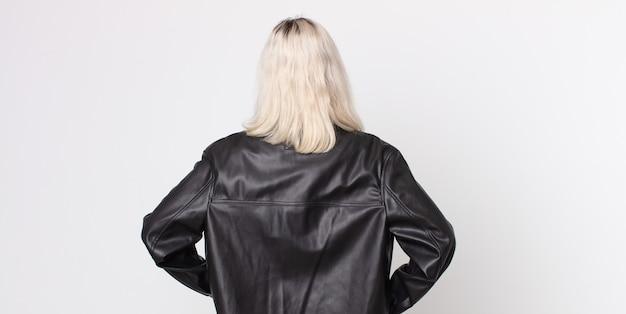 Mujer bonita albina que se siente confundida o llena o con dudas y preguntas, preguntándose, con las manos en las caderas, vista trasera