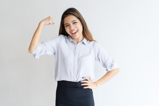 Mujer bonita alegre bombeando puño y celebrando logro