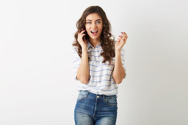Mujer bonita alegre con expresión de la cara emocionada riendo y hablando por teléfono, sonriendo sinceramente, cabello largo y rizado, estilo de estudiante, dientes blancos aislados, dama emocional