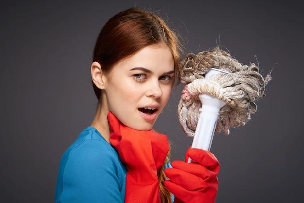 Mujer bonita alegre con una fregona en la mano con guantes de goma.