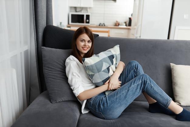 Mujer bonita con almohada en un cómodo sofá de manos.