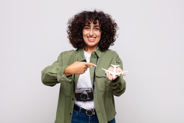 Mujer bonita árabe con un modelo de avión. concepto de traver