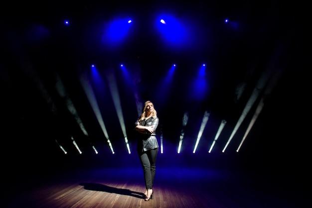 Mujer bonita artista sobre el fondo de focos borrosos en el escenario