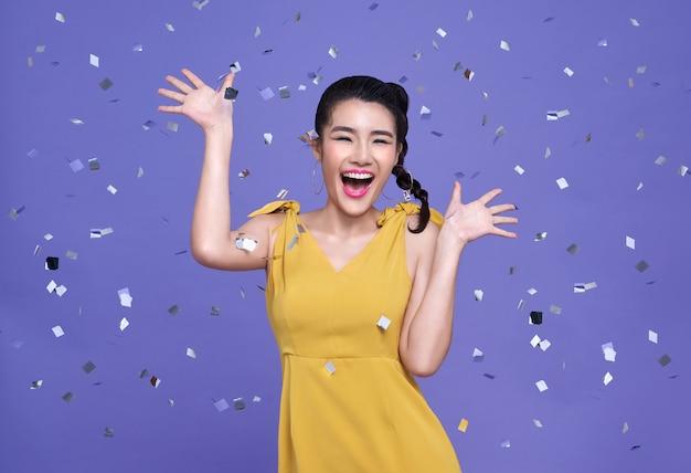 Mujer bonita asiática en celebración alegre con confeti cayendo sobre ella.