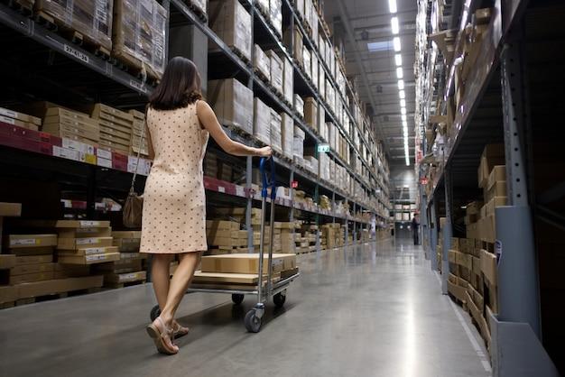 La mujer bonita asiática integral que empuja una carretilla está buscando algunos artículos en almacén