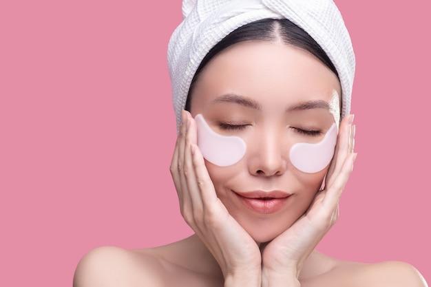 Mujer bonita asiática en un pañuelo blanco que se siente relajado