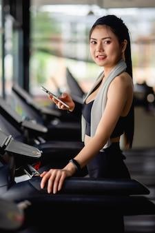 Mujer bonita asiática con ropa deportiva y reloj inteligente descansa en la cinta de correr, usa la aplicación de entrenamiento para teléfono inteligente y reloj inteligente y escucha música en el gimnasio moderno