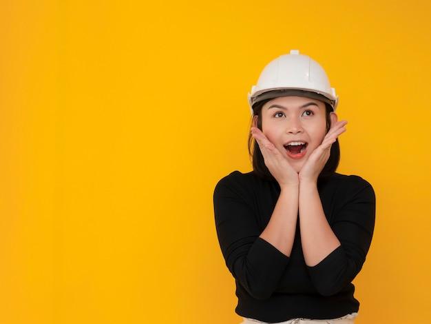 Mujer bonita asiática con sombrero de seguridad con cara de sorpresa