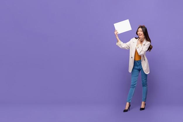 Mujer bonita asiática sonriente que sostiene el papel en blanco