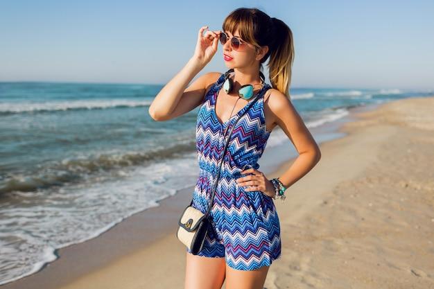 Mujer bonita con auriculares en la playa