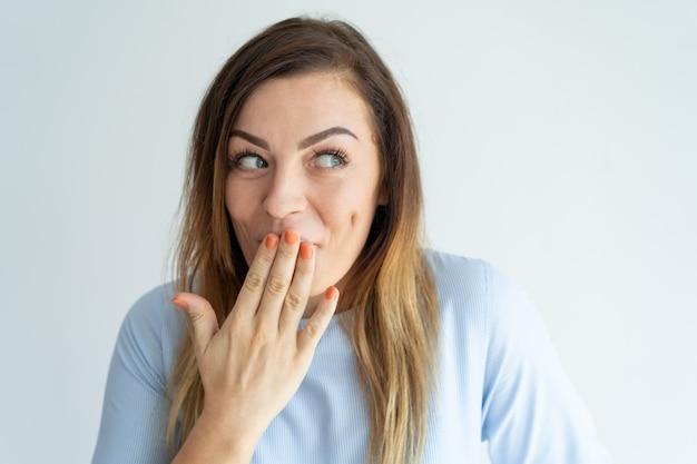 Mujer bonita avergonzada cubriendo la boca y mirando a un lado.