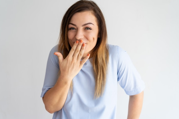 Mujer bonita avergonzada cubriendo boca y riendo