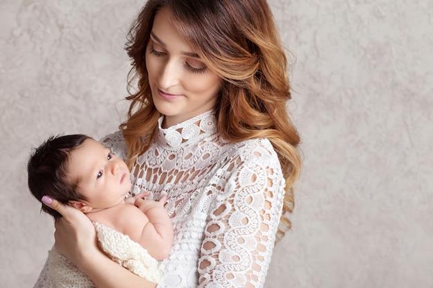 Mujer bonita con un bebé recién nacido en sus brazos. copia espacio
