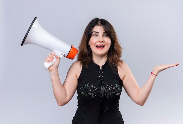 Mujer bonita en blusa negra con megáfono felizmente