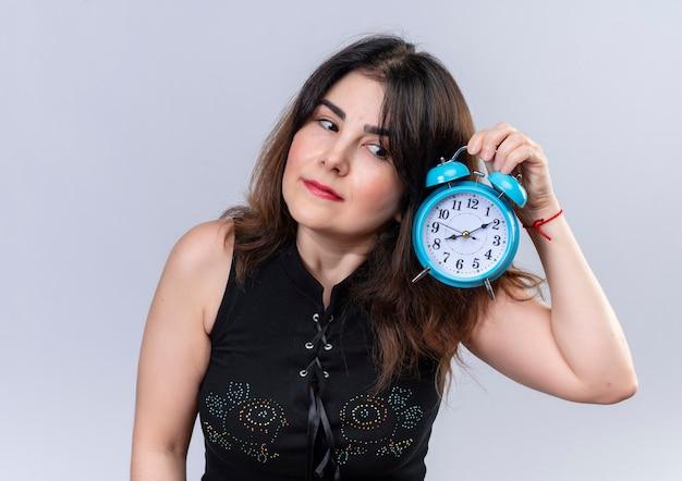 Mujer bonita en blusa negra preguntándose si el reloj está funcionando