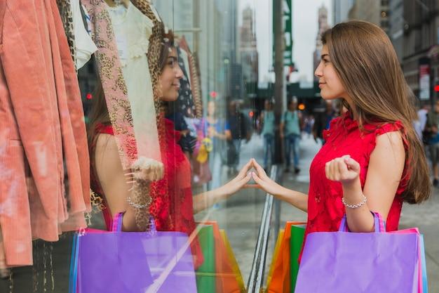 Mujer bonita con bolsas de compras cerca de la ventana de la tienda