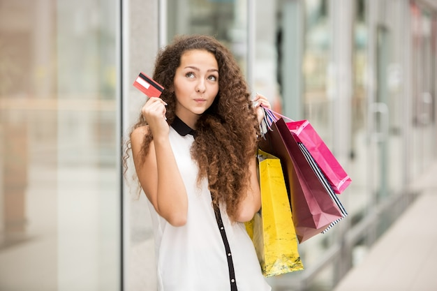 Mujer bonita con bolsas de compras y mostrando tarjeta de crédito en blanco