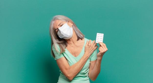 Mujer bonita de cabello gris con una máscara protectora y pastillas
