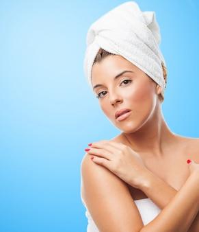 Mujer bonita con la cabeza torcida en una toalla.