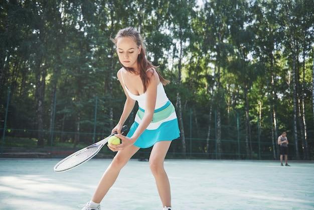 Una mujer bonita con una cancha de tenis de ropa deportiva en la cancha.