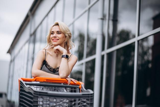 Mujer bonita con carrito de compras afuera