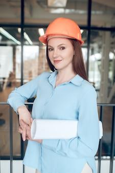 Mujer bonita en casco de seguridad con mirada segura