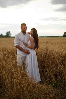 Mujer bonita caucásica con cabello largo ondulado oscuro en vestido blanco abraza con hombre hermoso en camiseta blanca y pantalones cortos