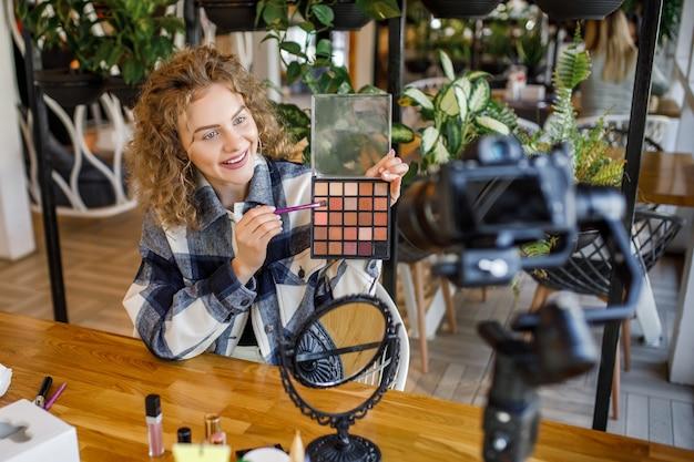 Mujer bonita caucásica, grabación de vlogger de belleza profesional maquillaje tutorial para compartir en las redes sociales