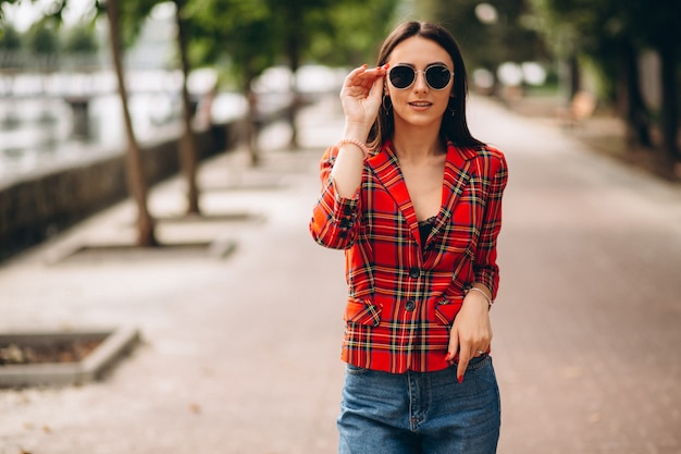 Mujer bonita en chaqueta roja afuera en el parque