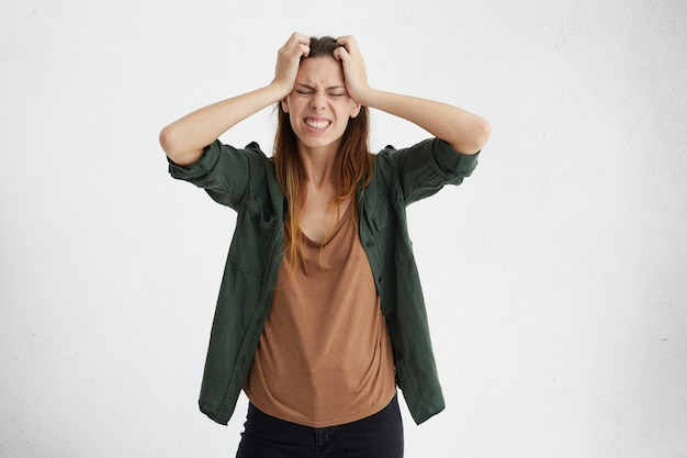 Mujer bonita cogidos de la mano en la cabeza con decepción y situación estresante que parece frustrada y llena de dolor, cerrando los ojos mientras llora