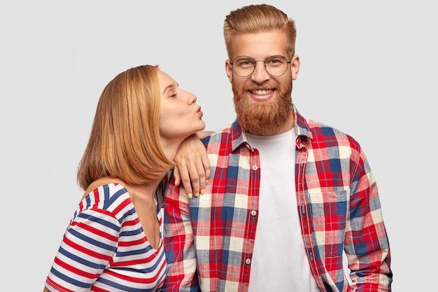 Mujer bonita complacida con peinado bobbed, se para de lado, se inclina sobre el hombro de su guapo novio barbudo