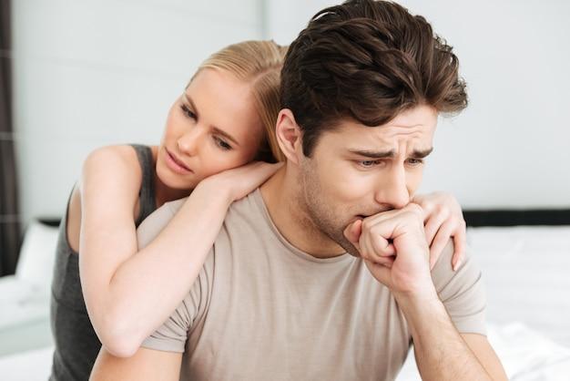 Mujer bonita consuela a su hombre triste mientras están sentados en la cama