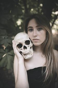 Mujer bonita con cráneo humano en el bosque