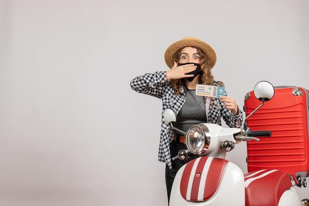 Mujer bonita desconcertada que sostiene el billete de pie cerca de la maleta roja del ciclomotor