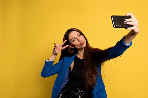 Mujer bonita divertida con cabello largo oscuro posando con expresión de la cara de besos. chica caucásica está haciendo un selfie.