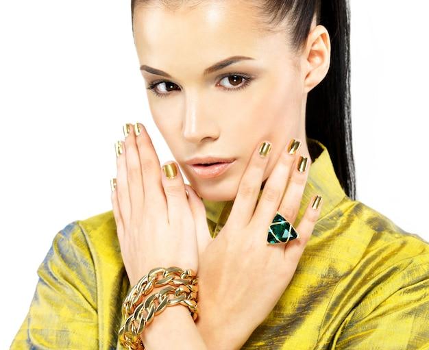 Mujer bonita con uñas doradas y hermosa piedra preciosa esmeralda - aislado sobre fondo blanco.