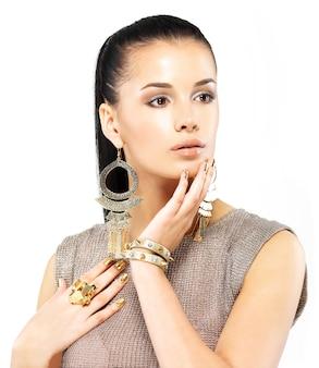 Mujer bonita con uñas doradas y hermosas joyas de oro aisladas en blanco