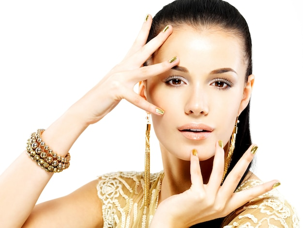 Mujer bonita con uñas doradas y hermosas joyas de oro aisladas en la pared blanca