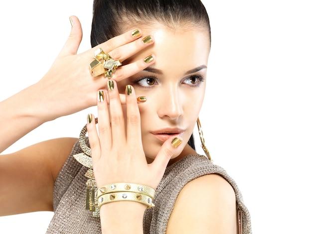 Mujer bonita con uñas doradas y hermosas joyas de oro aisladas sobre fondo blanco.