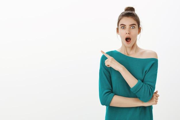 Una mujer bonita emocionada deja caer la mandíbula por el asombro, señala con el dedo en la esquina superior izquierda, un gran anuncio de noticias