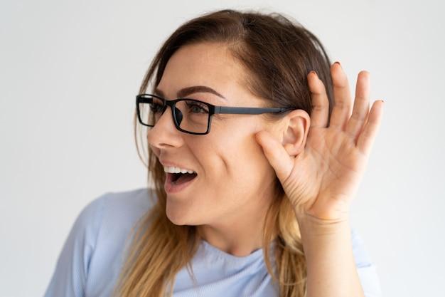 Mujer bonita emocionada que lleva a cabo la mano cerca de la oreja
