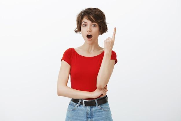 Una mujer bonita emocionada tiene una excelente idea, levanta el dedo en un gesto eureka, sugiere un plan