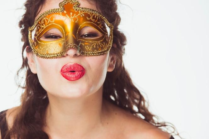 Mujer bonita en la máscara de besar el aire