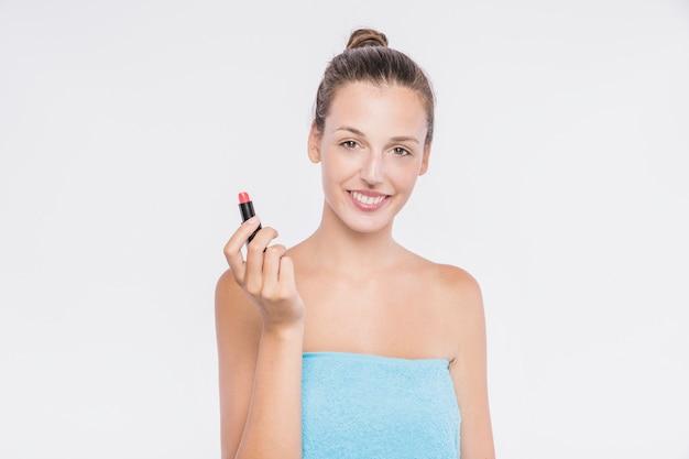 Mujer bonita en toalla con lápiz labial