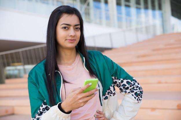 Mujer bonita en las escaleras mirando a cámara, sosteniendo el teléfono en la mano