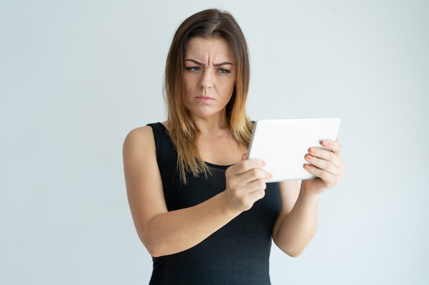 Mujer bonita escéptica que lee noticias en la tableta. señora navegando en tableta.