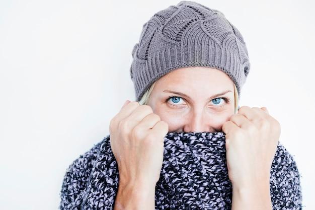 Mujer bonita escondiendo la cara detrás de la bufanda
