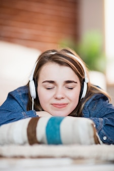 Mujer bonita escuchando música tirada en el suelo en la sala de estar
