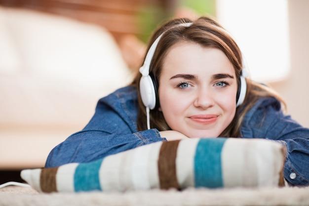 Mujer bonita escuchando música tirada en el suelo